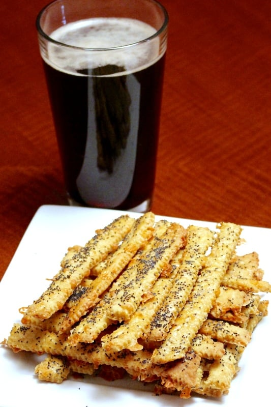 Cheese straws with cumin on white platter with a glass of dark beer in the background