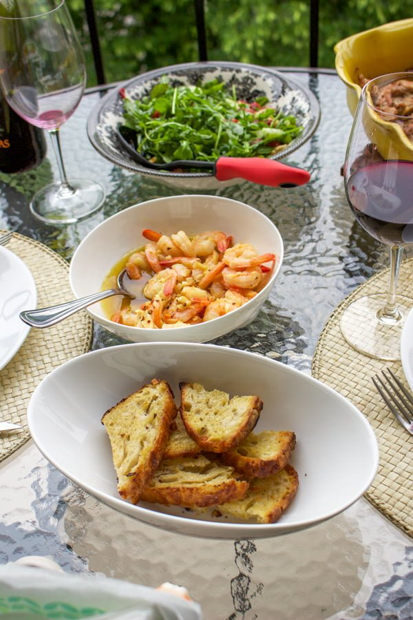 Sizzling Chili Shrimp-Spanish Recipe,  or Gambas al Pil Pil on table with bread and salad in the background