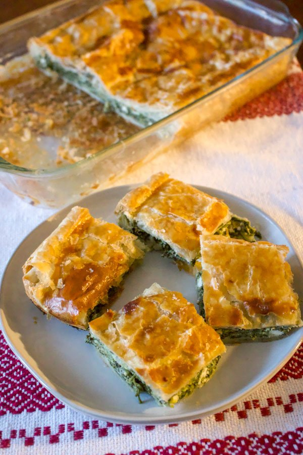 This Romanian Spinach And Feta Cheese Pie is a rustic recipe that is made with puff pastry. A wonderful, relatively easy recipe to make, suitable for vegetarians, this pie is made with spinach, leeks, onions, dill and mint.