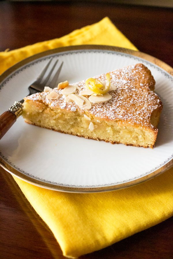 Spanish Almond Cake Recipe Tarta de Santiago- slice on white plate with yellow towel and fork