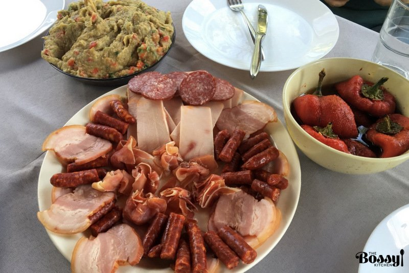cold cuts on a platter with roasted pepper salad and eggplant spread