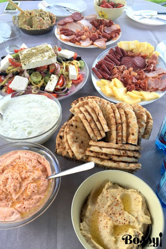 salads, cold cuts, dips and sauces served on platters sitting on table