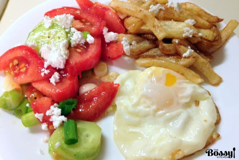 Tomato Cucumbers Feta Salad served with fried egg and French fries on a white plate