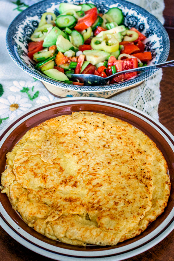 cheese pie on a plate with vegetable salad in the background