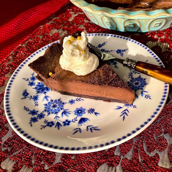 Slice of chocolate tart on blue and white plate-close up square picture