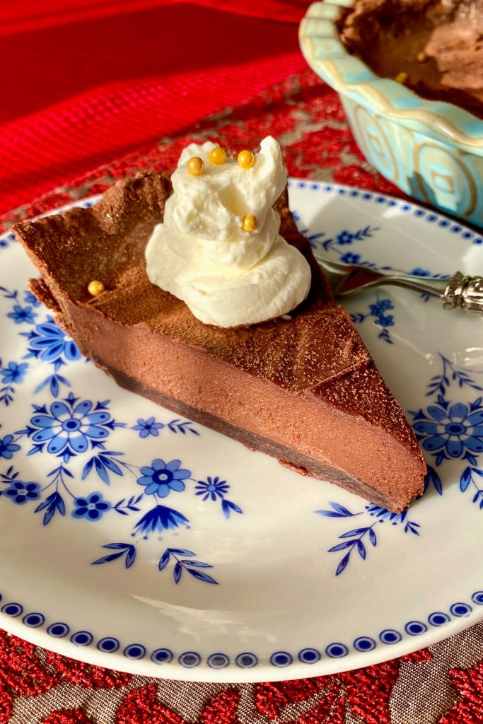 slice of chocolate tart with whipped cream on top