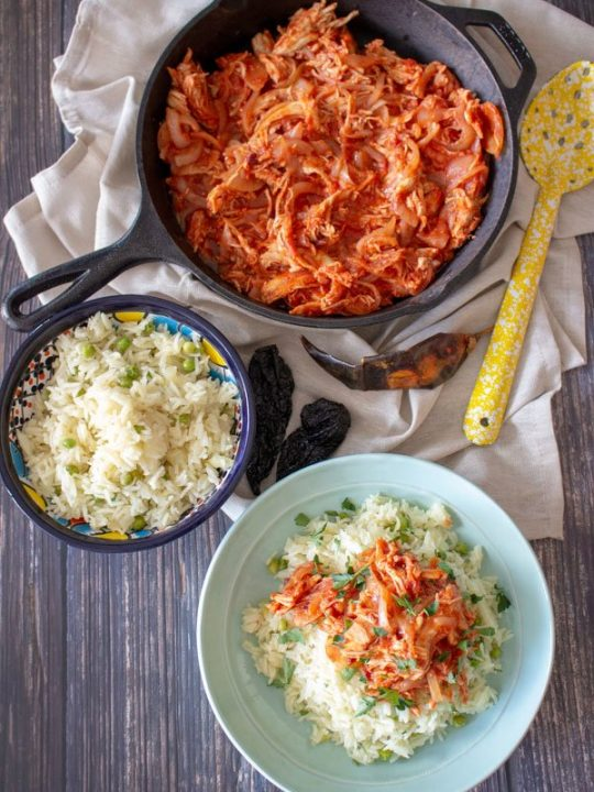 Mexican rice bowl, Mexican rice with Tinga de pollo on a blue plate with Tinga in the background with yellow spoon