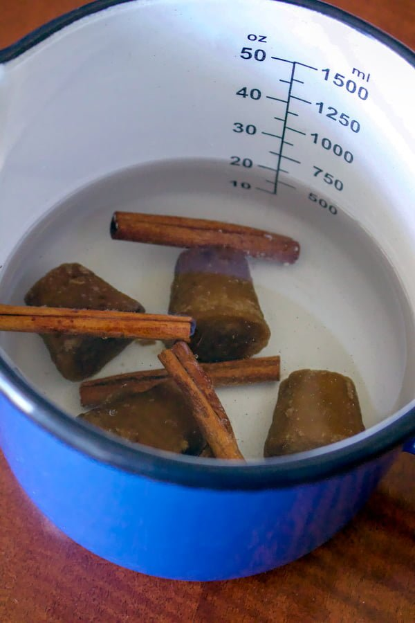 Authentic Mexican Capirotada- Bread Pudding - piloncillo and cinnamon sticks cooking in a pot with water