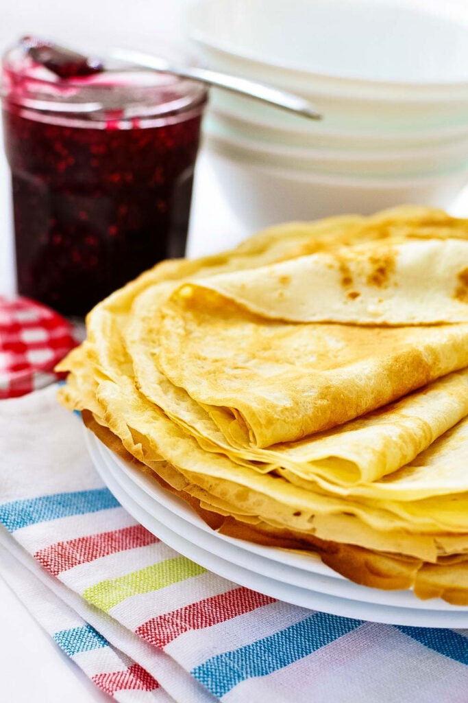 Crepes with a jar of raspberry jam in the background0