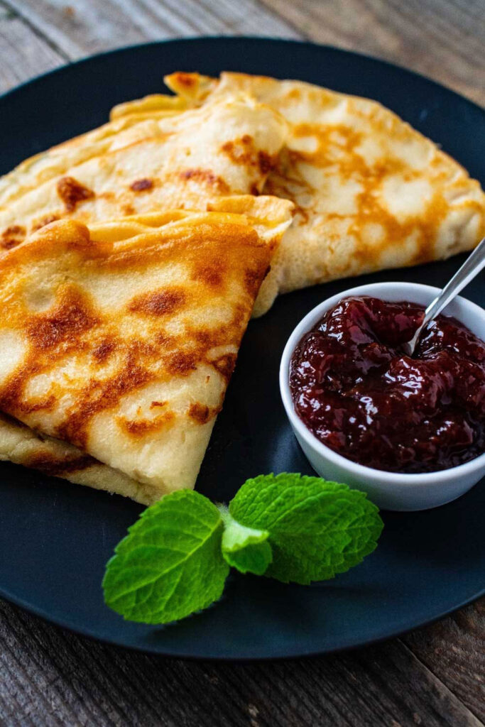 Crepes with jam on a dark plate0