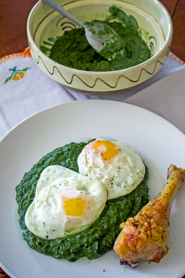 Easy creamed spinach served with fried eggs and chicken on a white plate