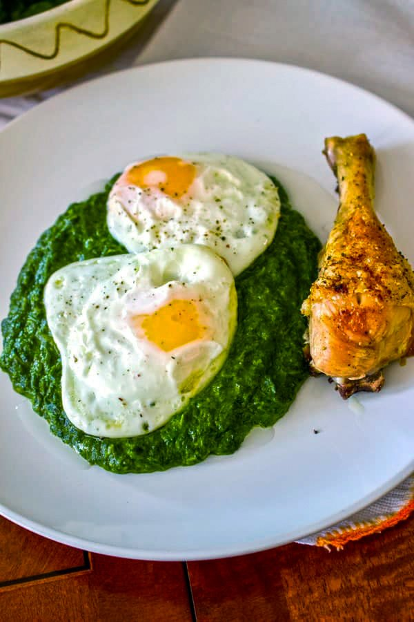 Easy creamed spinach on a white plate with fried eggs and a fried chicken leg