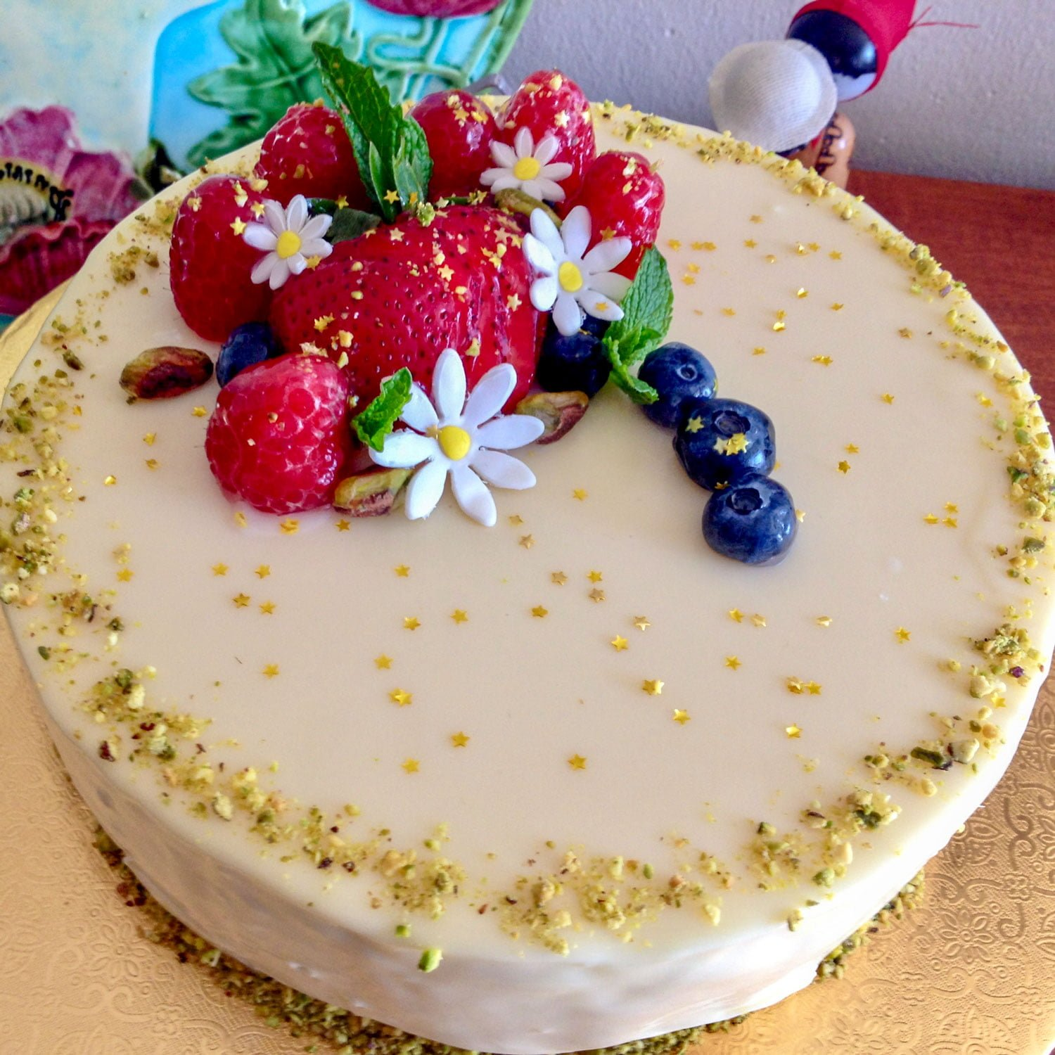 White Chocolate Hazelnuts Dacquoise Cake is a recipe of hazelnut Dacquoise cake with white chocolate mousse, a strawberry compote, pistachios, all covered in a white chocolate glaze, decorated with berries and edible gold sprinkles.