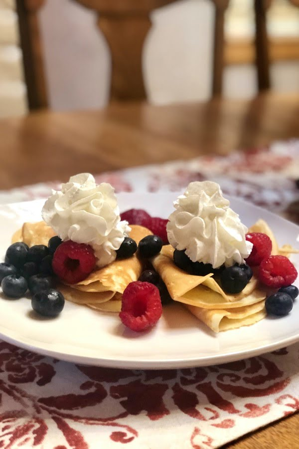 folded crepes with berries and whipped cream