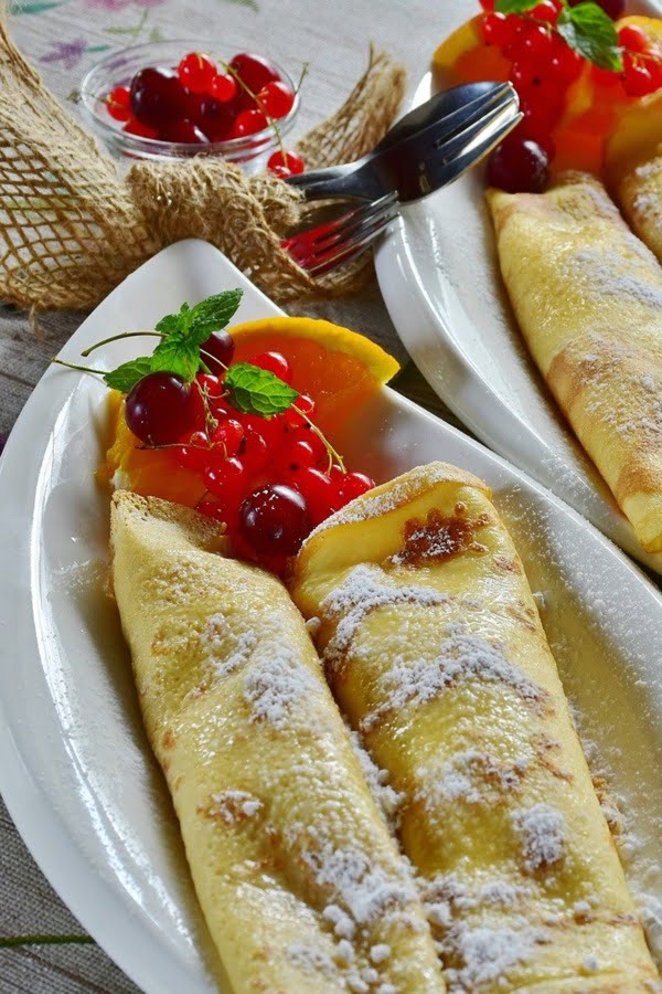 Crepes on a plate with powder sugar on top