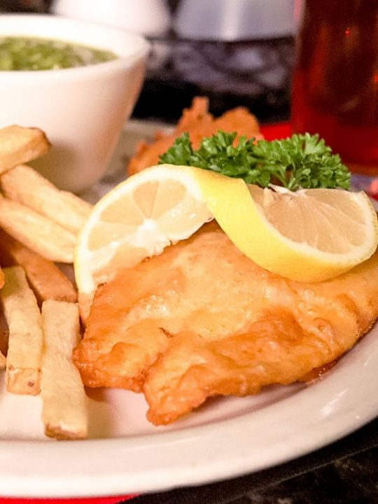 Fried fish on a plate served with lemon wedges and French Fries