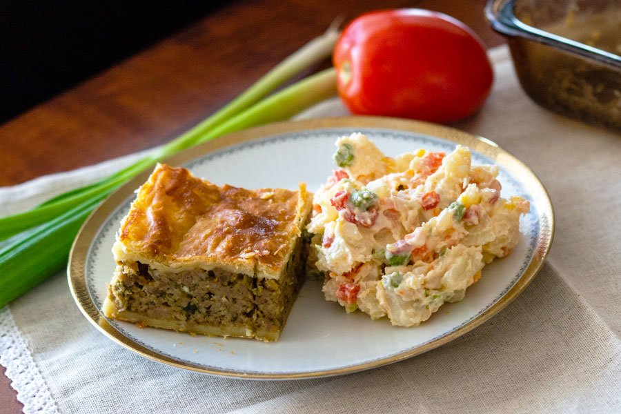 Slice of Puff Pastry Minced Meat Pie on a white plate with golden rim next to potato salad- with green onions and a tomato in the background