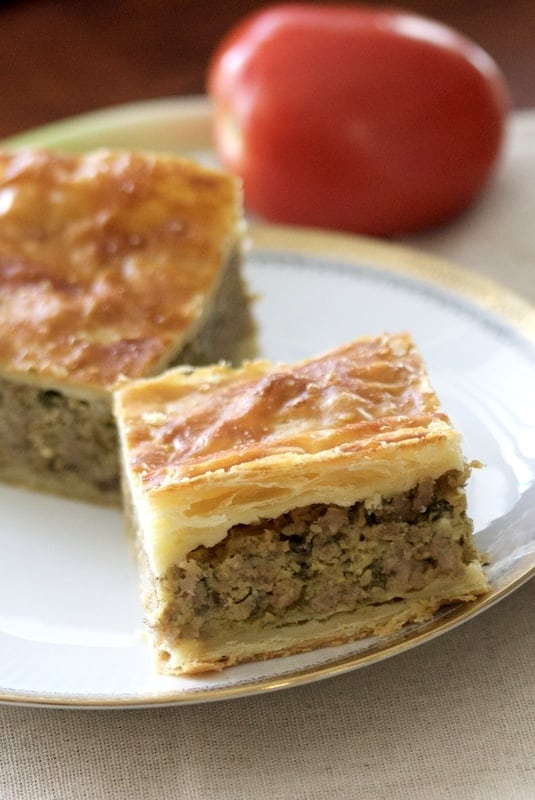 This Romanian Perfect Easter Puff Pastry Minced Meat Pie recipe is a cousin of the Greek Kreatopita pie and a delicious dish I make every Easter. The pie is made with puff pastry and a filling of ground meat that can be pork, beef, or a combination of both. It works great as an appetizer for the Easter meal.#easter #easyrecipes #meatpie #puffpastry