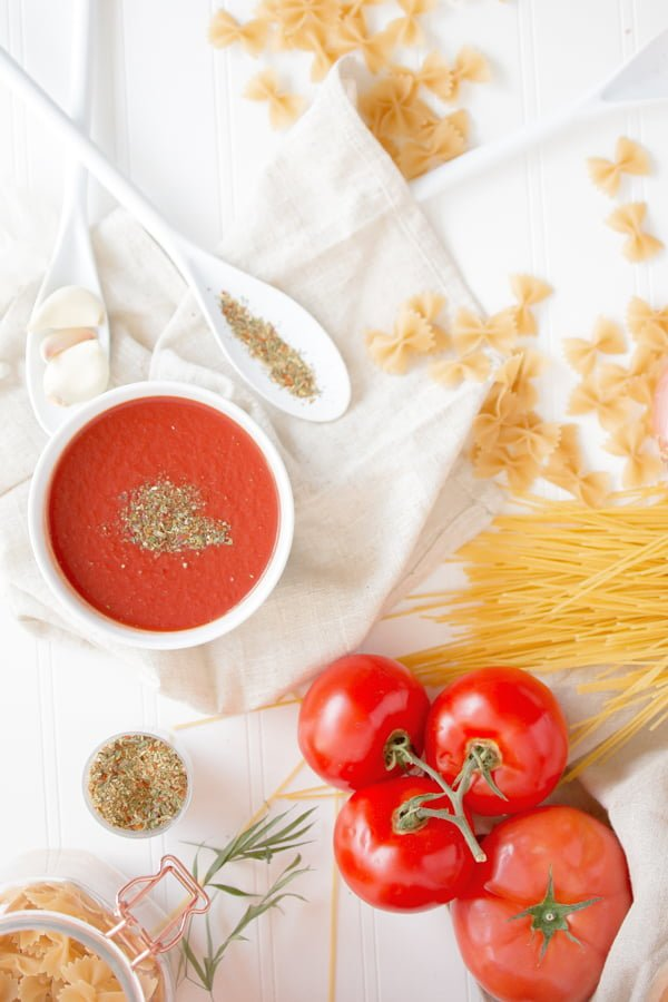 Romanian Tomato Soup Dairy Free- on a white table decorated with pasta
