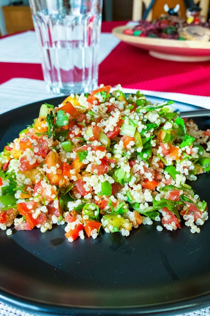 Quinoa Tabbouleh Salad on a black plate- featured picture