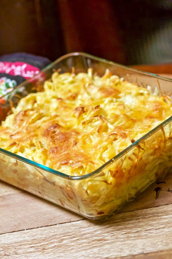 Baked cheesy German Spaetzle pasta with caramelized onion- out of the oven on a wooden board
