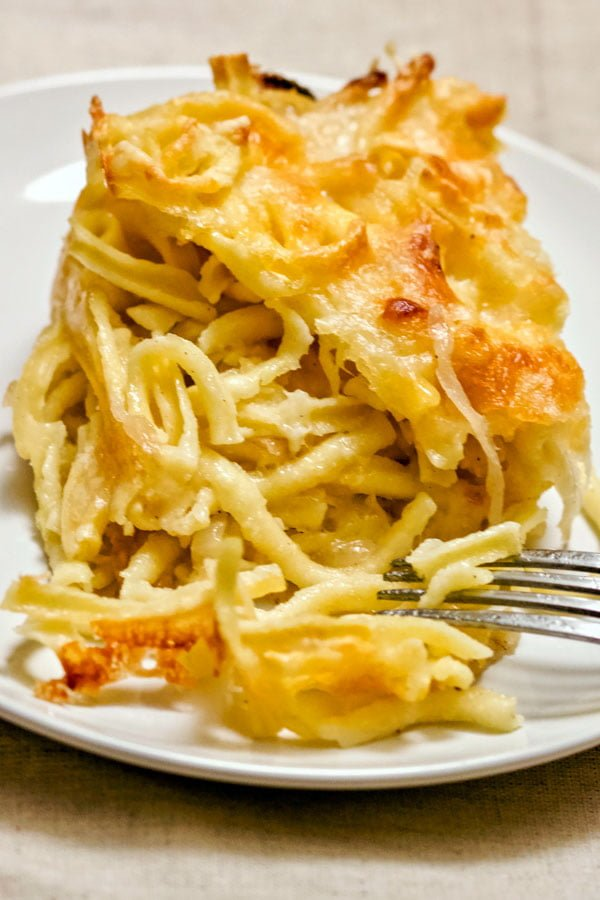 Baked cheesy German Spaetzle pasta with caramelized onion- on a white plate
