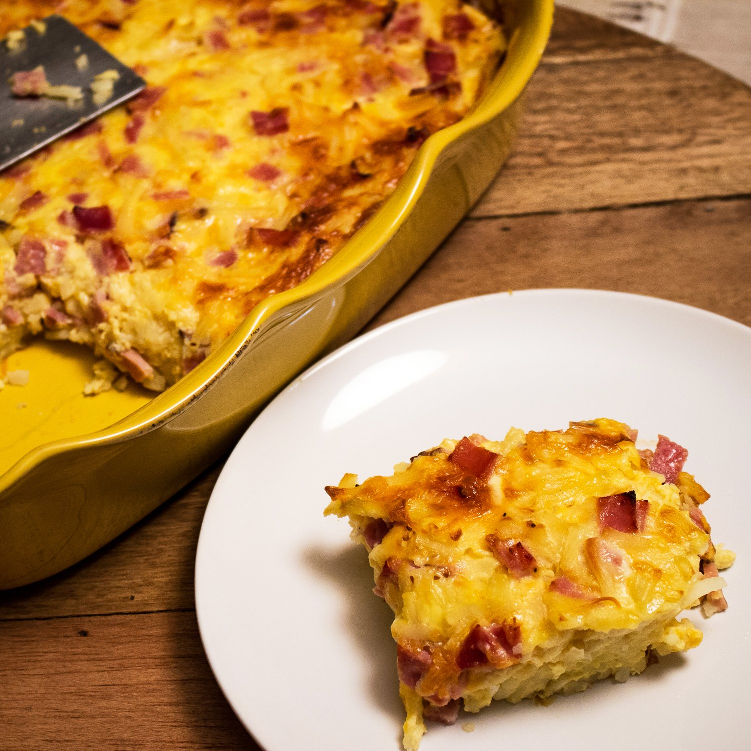 Delicious breakfast recipe- Cheesy Ham Hash Brown Egg Casserole- on a white plate with the baking dish in the background