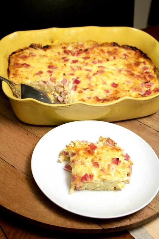 Cheesy Ham Hash Brown Egg Casserole- served on a white plate with yellow baking dish in the background