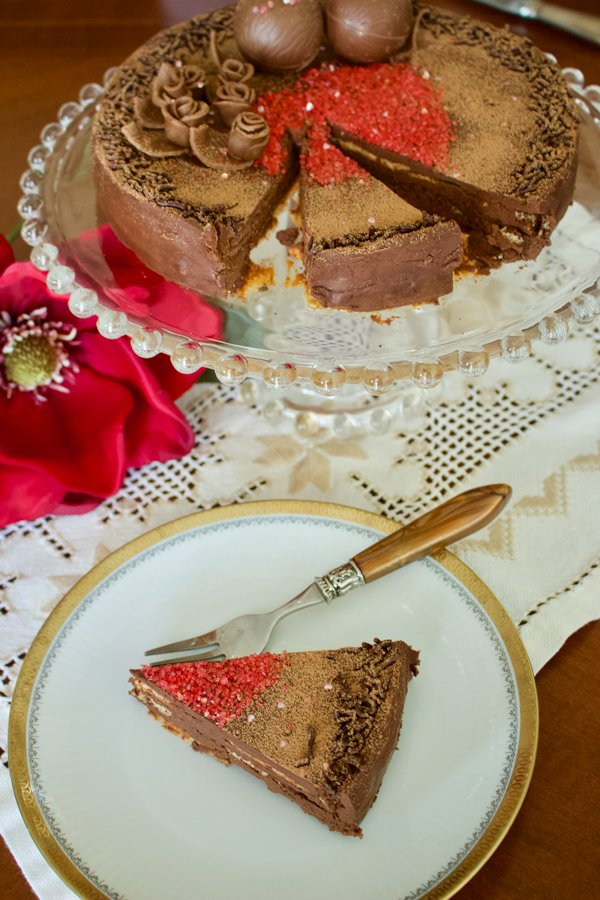 Classic European chocolate ganache meringue torte- slice of cake on a white plate with fork . Cake sitting on a cake platter in the background- overhead picture