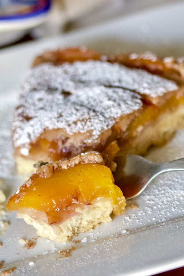 German Peach Kuchen- a Transylvanian dessert made with peaches, custard and a shortbread crust. Delicious, easy to make and perfect for summer.