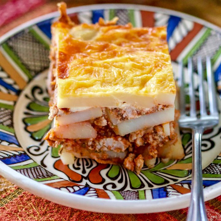 Piece of Romanian Authentic Potato Moussaka on colorful plate with fork