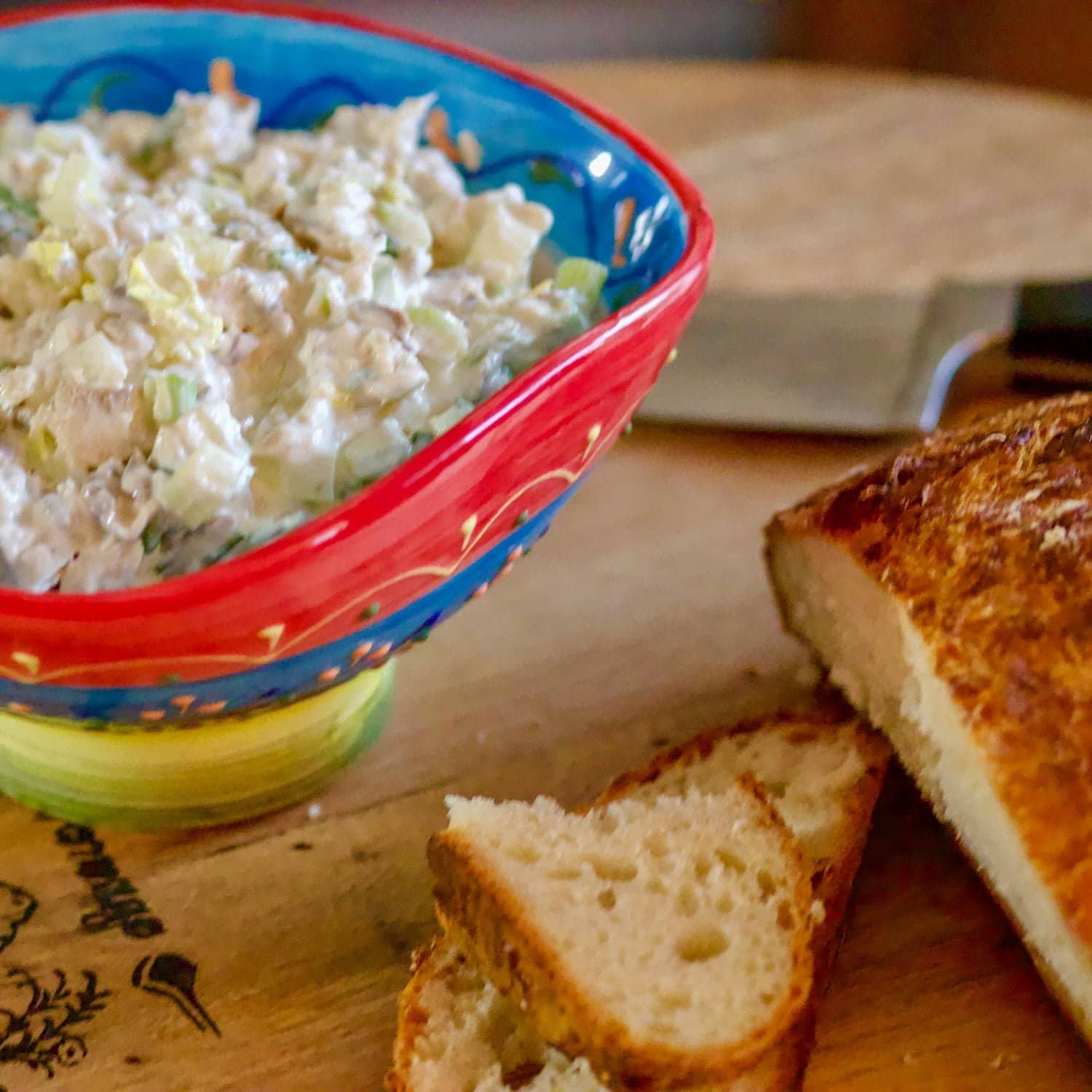Smoked trout dip with mayo in a colorful bowl next to crusty bread