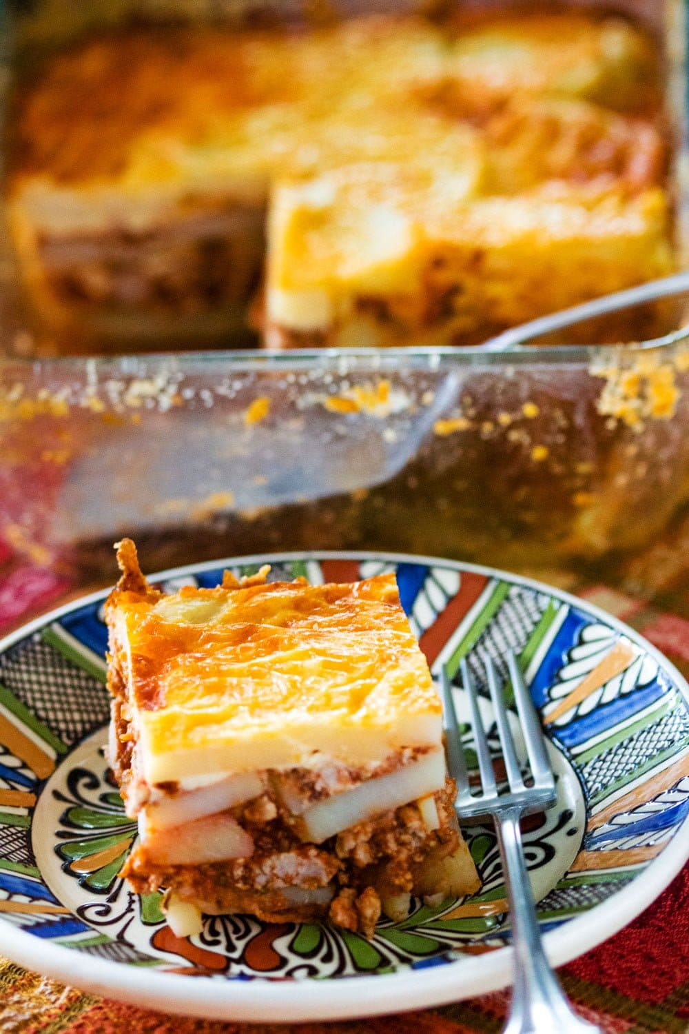 Romanian Authentic Potato Moussaka- Pinterest featured picture- piece of moussaka served on a colored plate with fork- bake tray in the background