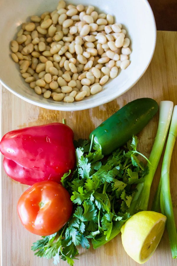 white bowl with beans in the background plus peppers, tomatoes, cilantro and onion with half lemon on wooden board