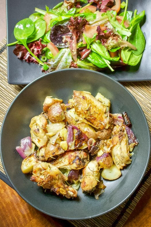 Lemon Rosemary Roasted chicken with Potatoes and Red Onion- in a black plate with salad