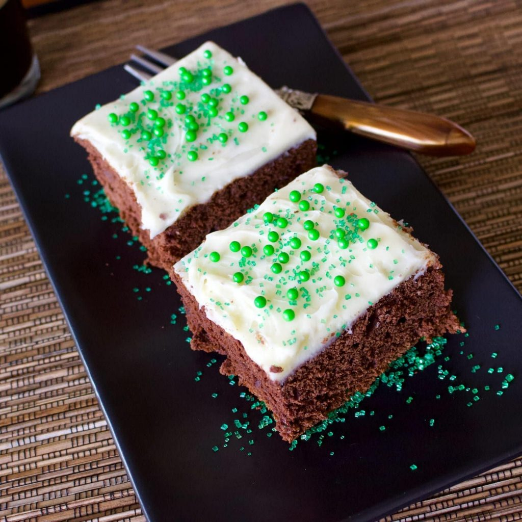 Chocolate Stout Cake With Cream Cheese Frosting- on a black long plate with a fork