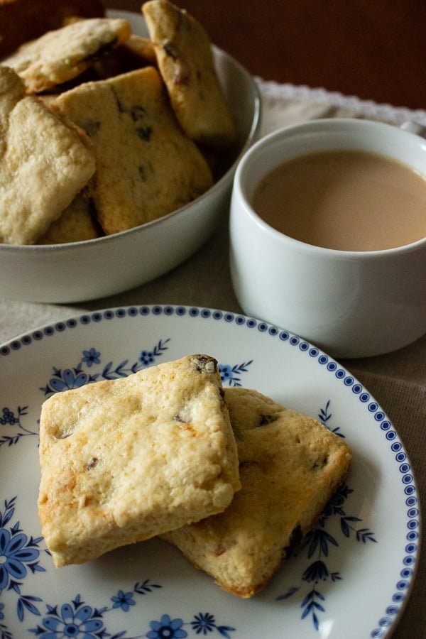 Apricot And Sour Cream Scones scones on a white and blue plate and a white cup with coffee and milk