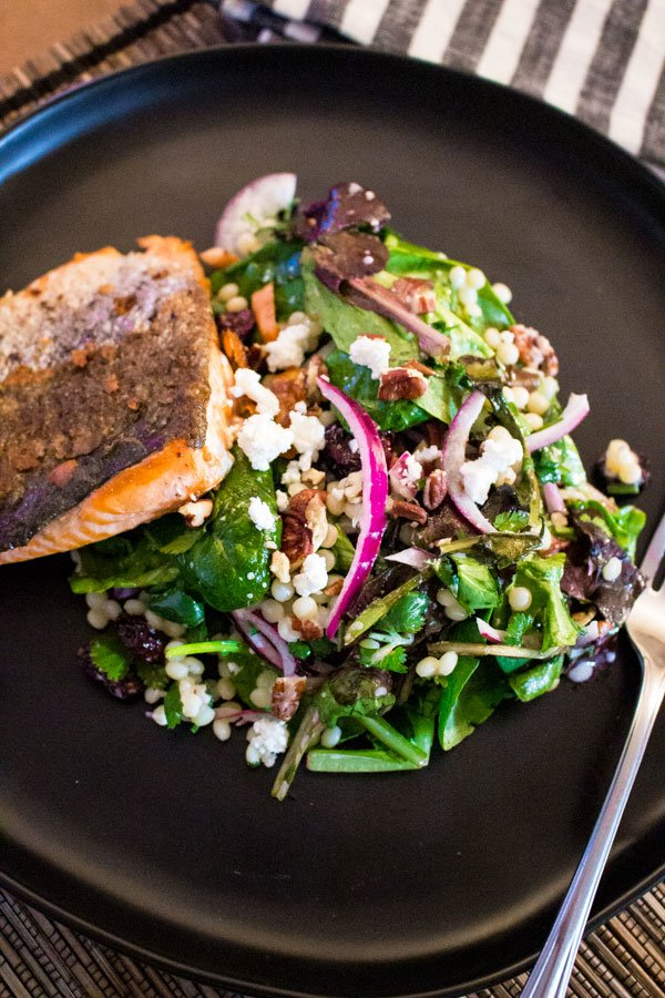 Fresh Baby Spring Greens Couscous Pecans Salad With Grilled Salmon- on a black plate