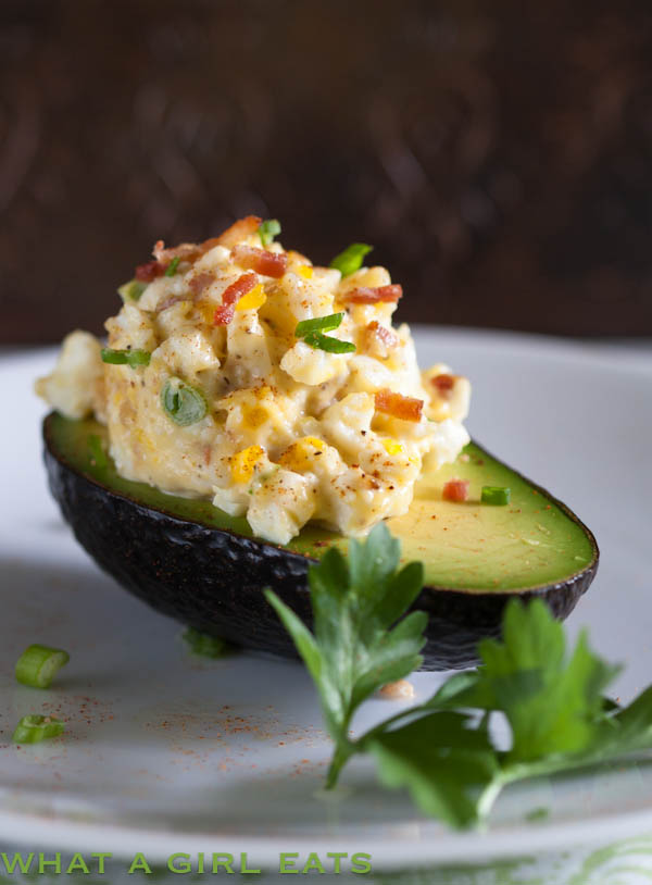 Egg salad with bacon is a delicious spin on a traditional egg salad recipe. Creamy egg salad and crisp bacon, combined and served in fresh avocado halves.   @whatagirleats