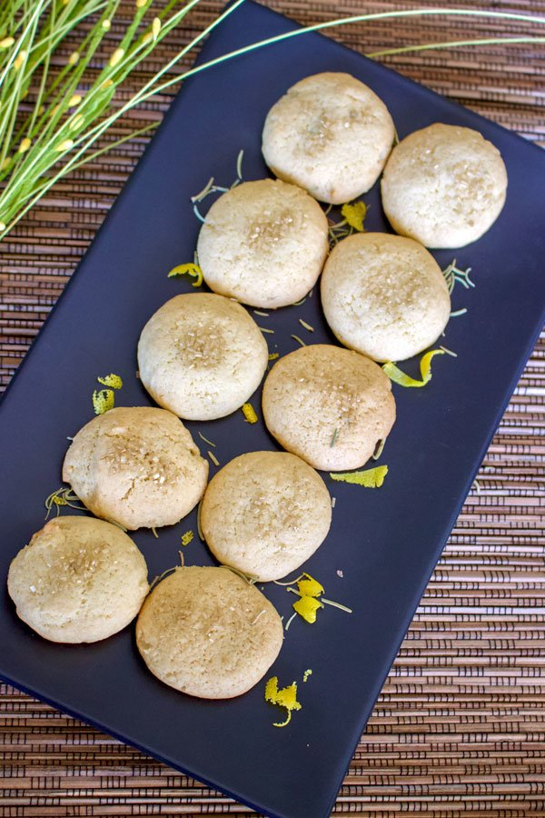 Olive oil lemon cookies with herb- 10 lined up cookies on a black long platter