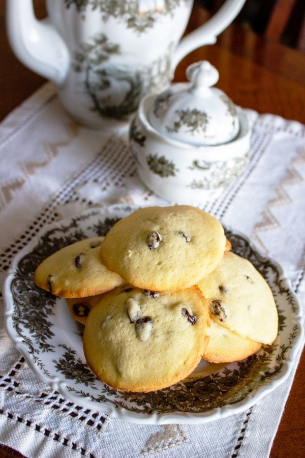 rum raisins cookies on a white and grey plate next to a tea pot