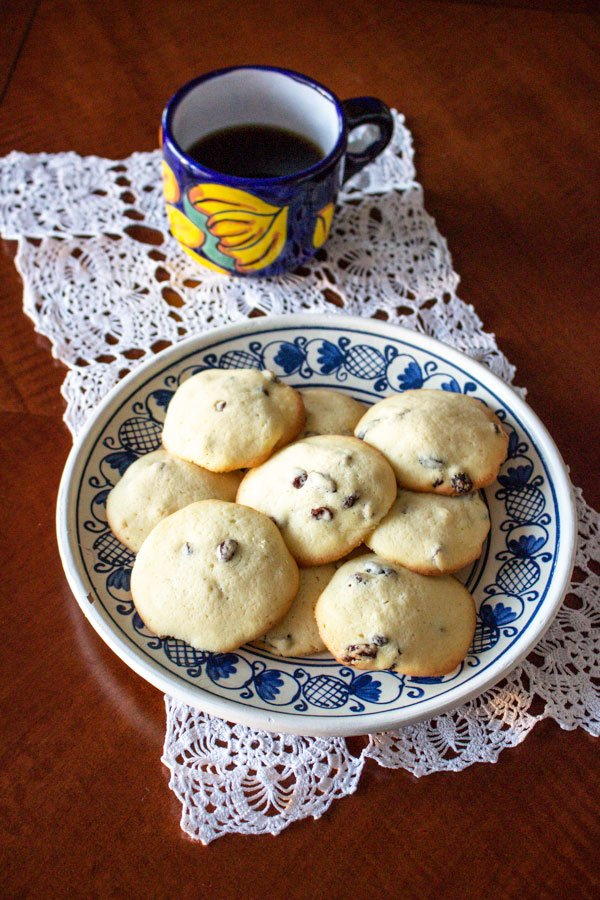 rum raisins cookies  on a blue and white plate with a colorful coffee mug on a wooden table