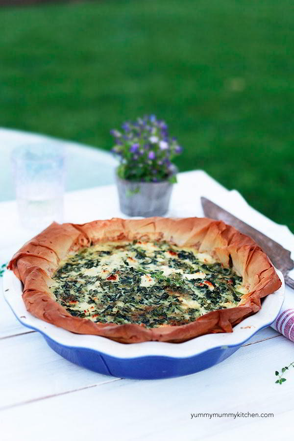 Spinach quiche with filo crust on a white background outside.