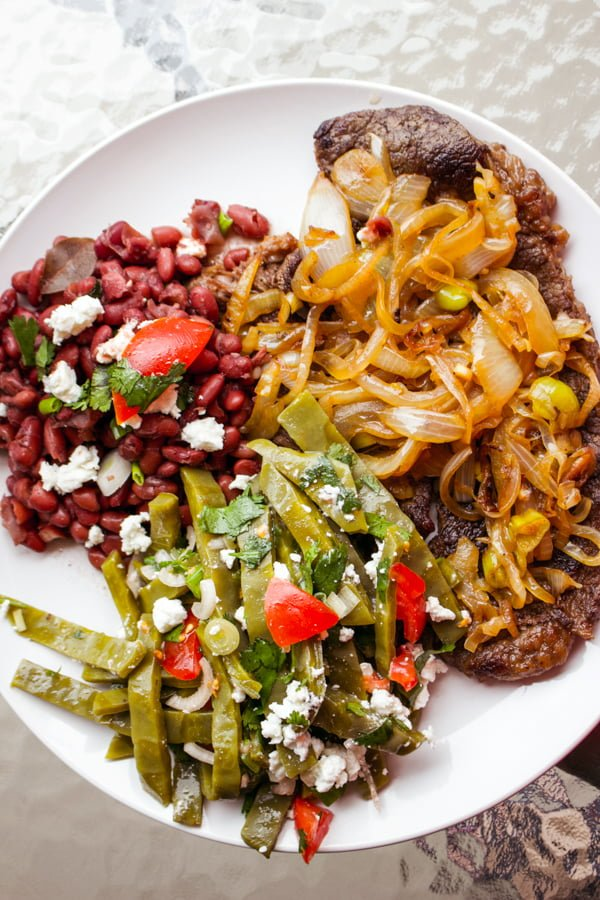 beans, steak and nopales salad on a white plate