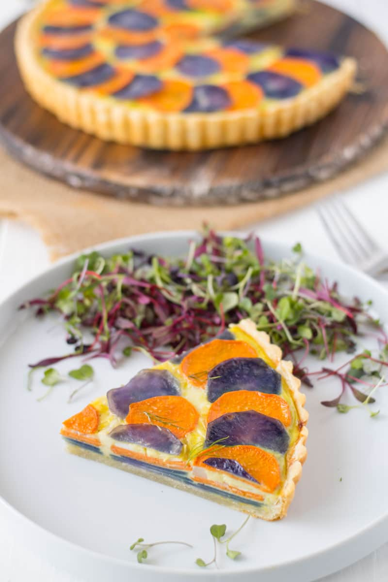 a slice pf Potato and vegetable quiche on a plate with micro greens