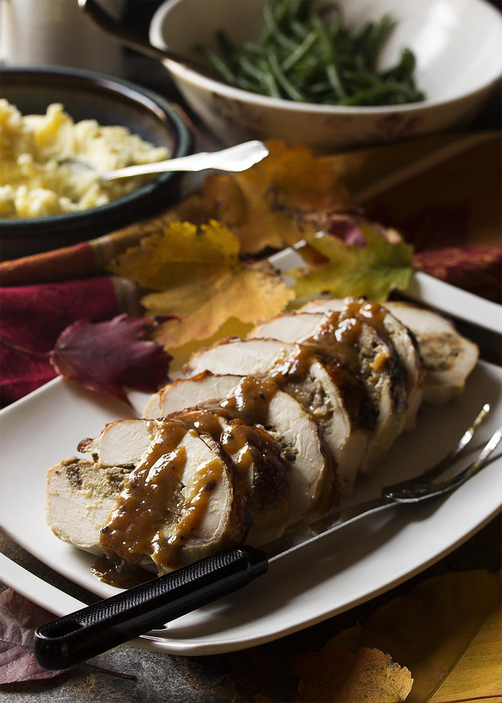 My fig and sausage stuffed turkey breast roulade makes an impressive main course which is perfect for Thanksgiving or Christmas holiday dinner. And while it rests you can make a white wine gravy from the drippings! | justalittlebitofbacon.com