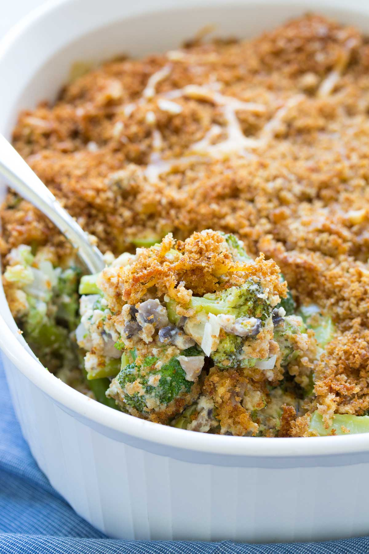 This delicious broccoli casserole from scratch is filled with fresh broccoli, mushrooms, cheddar cheese, and a homemade cream sauce. A buttery, cheesy breadcrumb topping adds a crispy finishing touch to this classic dish. This healthier broccoli casserole is made without mayonnaise.