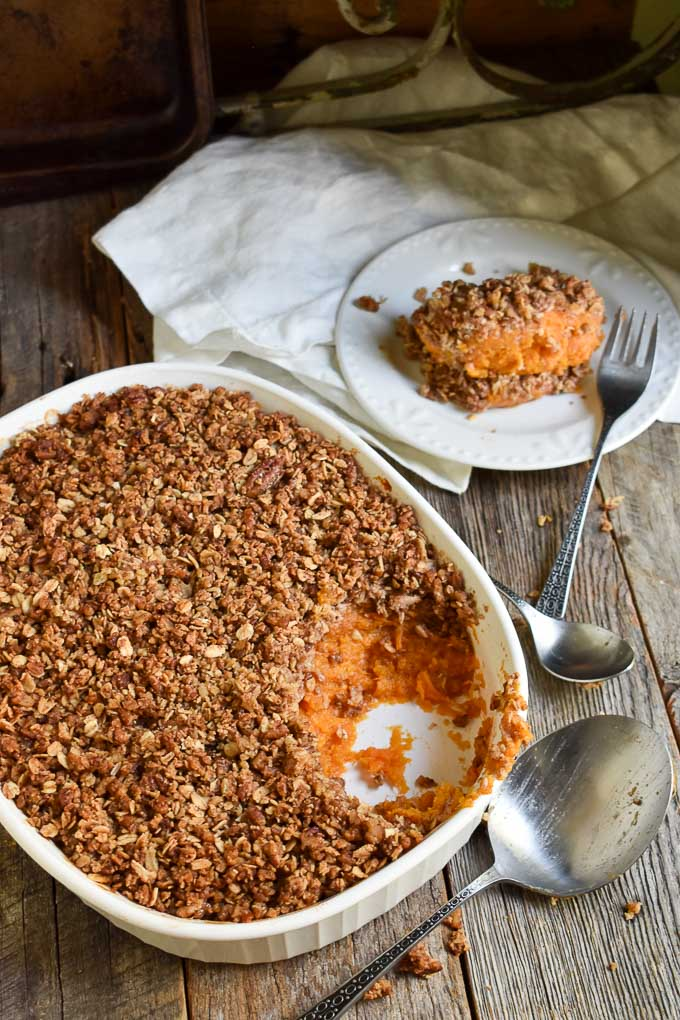 Vegan Sweet Potato Casserole on table with serving dish and plate