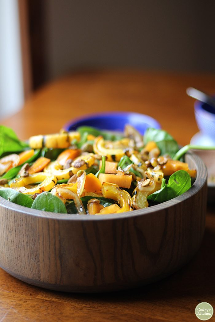 Brown bowl with fall squash salad, including spinach and persimmons.