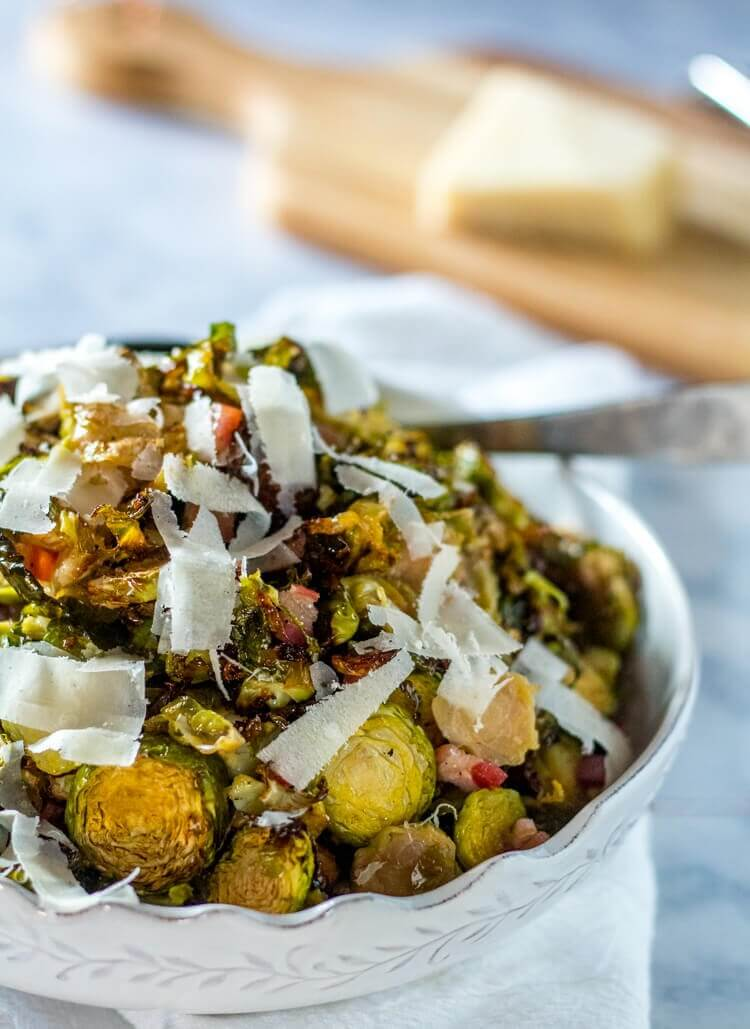 Roasted Shredded Brussels Sprouts with Pancetta and Pecorino - A close up of a white bowl piled high with brussels sprouts with a wood cutting board and pecorino in the background.
